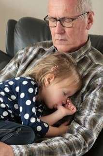 grandfather asleep with grandchild on his lap