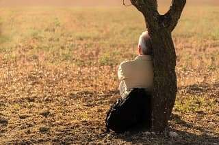 lonely man leaning against a tree