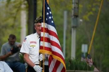 military veteran standing by an American flag